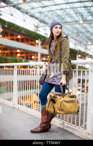Full length of woman with luggage leaning on railing at airport - Stock Photo