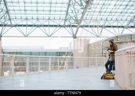 Side view of woman with luggage using mobile phone while leaning on railing at airport - Stock Photo