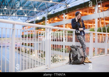 Happy woman talking on mobile phone while leaning by railing at airport - Stock Photo