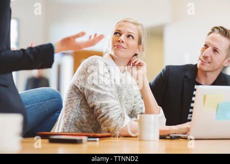 Colleagues looking at businesswoman talking while sitting on table in office - Stock Photo