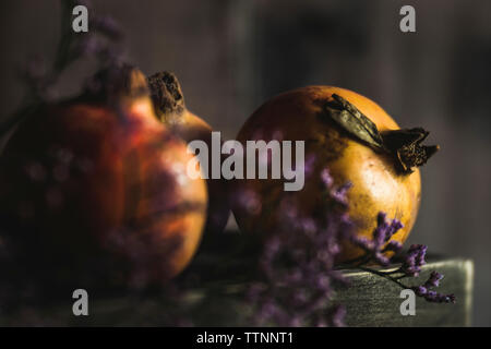 Close-up of healthy pomegranates with flowers on wooden table - Stock Photo