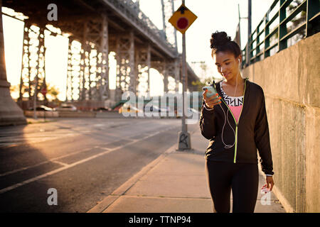 Female jogger text messaging while walking on sidewalk - Stock Photo