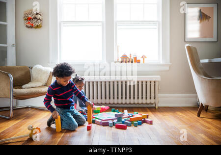 Brother and sister playing on floor at home - Stock Photo