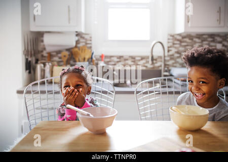 Cheerful brother and sister looking away while having breakfast in kitchen - Stock Photo