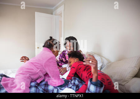 Cheerful family spending leisure time in bedroom - Stock Photo