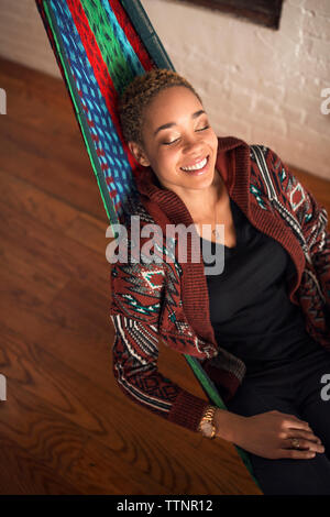 Overhead view of happy woman sleeping on hammock at home - Stock Photo