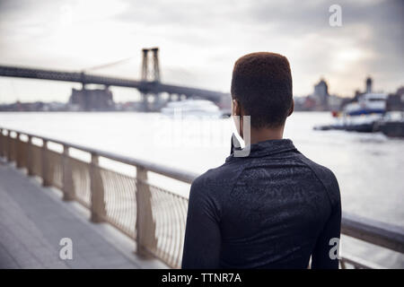 Rear view of female athlete walking on footpath with Williamsburg Bridge in background - Stock Photo