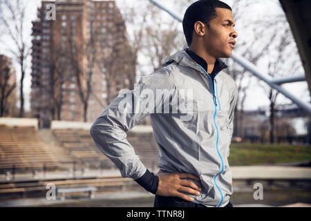 Thoughtful male athlete standing with hand on hip at park - Stock Photo