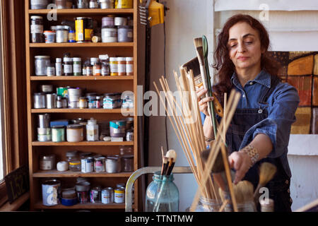 Artist holding paintbrushes in workshop - Stock Photo