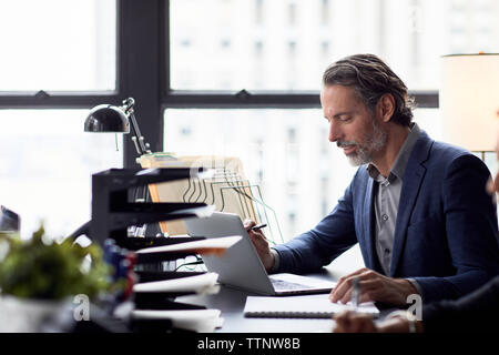 Businessman working on laptop computer against window in office