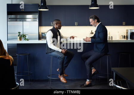 Male colleagues talking while sitting on stools at kitchen counter in creative office - Stock Photo