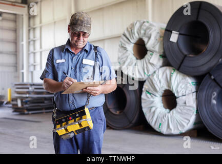 Manual worker writing on clipboard while working in metal Steel Industry Factory - Stock Photo