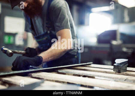 Midsection of blue collar worker using hammer and chisel in steel factory - Stock Photo