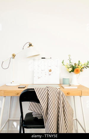 Technologies with calendar and desk lamp by flower vase on table in office - Stock Photo