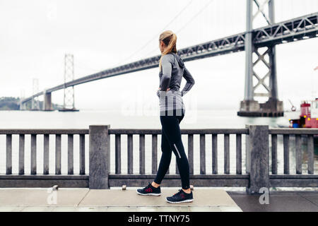 Side view of female athlete looking at Oakland Bay Bridge while standing on footpath - Stock Photo