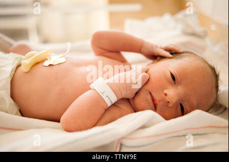 Close-up of newborn baby lying on hospital bed