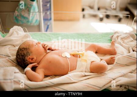 High angle view of newborn baby girl sleeping in hospital - Stock Photo