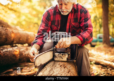 Mature male lumberjack examining chainsaw while sitting on log in forest - Stock Photo