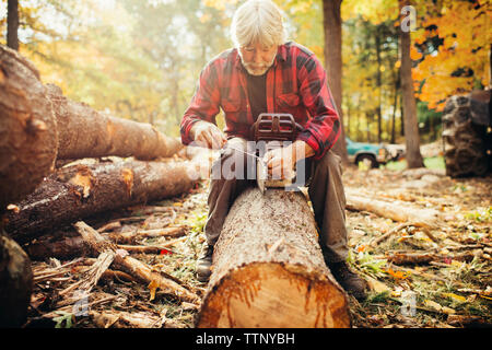 Mature male lumberjack fixing chainsaw while sitting on log in forest - Stock Photo