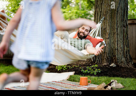 Low section of daughter running towards father relaxing on hammock at yard - Stock Photo