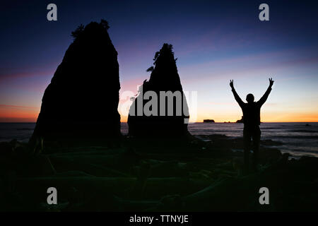 Silhouette man standing with arms raised on shore during sunset - Stock Photo