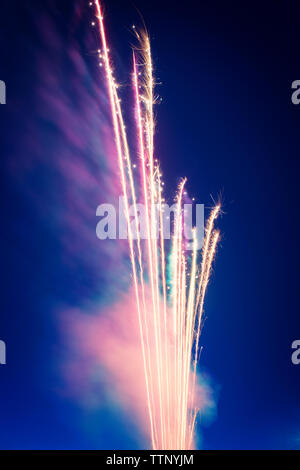 Low angle view of firework display against sky at night - Stock Photo