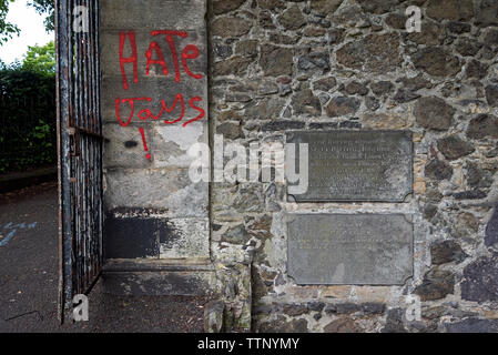 Homophobic graffiti painted on tombs in New Calton Burial Ground, Edinburgh, Scotland, UK. June 2019. - Stock Photo
