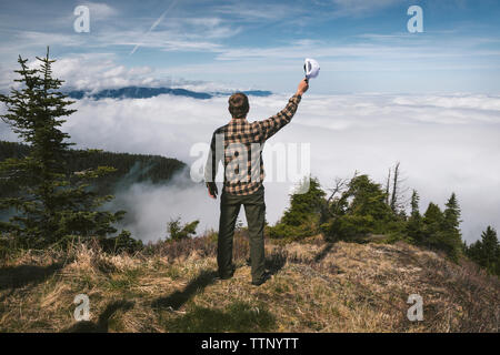 Rear view of man holding cap and standing on cliff against cloudscape - Stock Photo