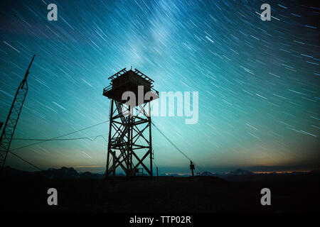 Low angle view of silhouette lookout tower against sky at night - Stock Photo