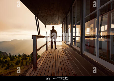 Rear view of man standing on balcony of cottage against sky - Stock Photo