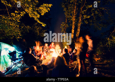 Friends sitting around campfire in forest - Stock Photo
