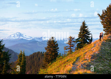 Hikers looking at view while standing on mountain during sunset - Stock Photo