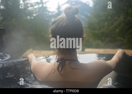 Rear view of woman bathing in hot spring - Stock Photo