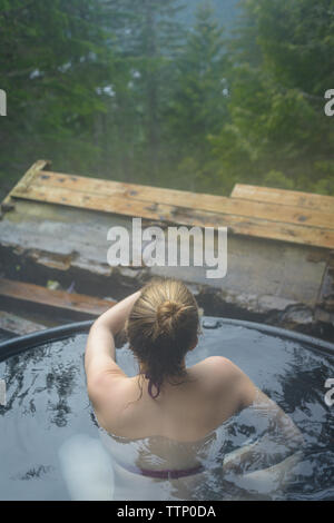 High angle view of woman bathing in hot spring - Stock Photo