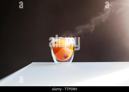 Smoke emitting from drink on table against black background - Stock Photo