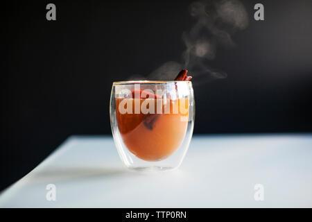 Smoke emitting from drink against black background - Stock Photo