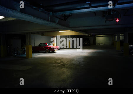Car parked in illuminated parking lot - Stock Photo