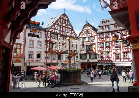 BERNKASTEL-KUES, RHINELAND-PALATINATE, GERMANY - MAY 31, 2019: Sightseeing tourists at the Market Square with half-timbered houses on a sunny afternoo - Stock Photo