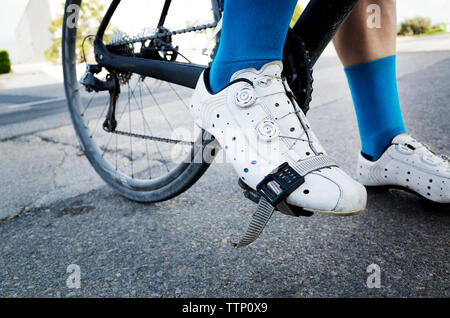 Low section of man riding bicycle on street - Stock Photo