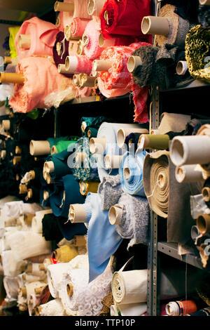 Rolled up fabrics in shelf - Stock Photo