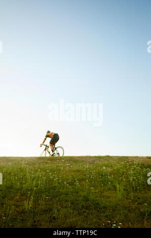 Low angle view of cyclist on grassy field against clear sky - Stock Photo