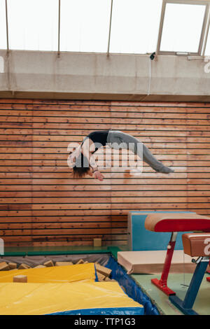 Side view of gymnast jumping from gymnastics equipment at gym - Stock Photo