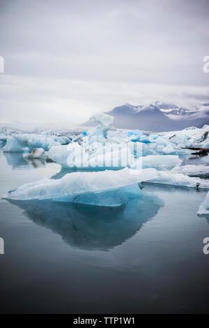 Scenic view of Jokulsarlon against cloudy sky - Stock Photo