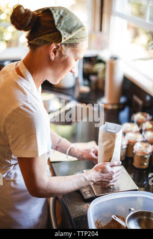 Woman packing mason jar while measuring on weight scale at kitchen counter - Stock Photo