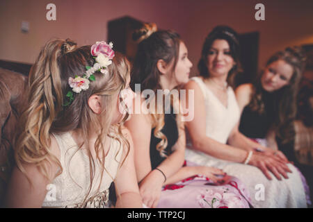 Bride with bridesmaids and flower girl sitting at home - Stock Photo
