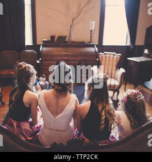 Rear view of bride with bridesmaids and flower girl sitting on sofa at home - Stock Photo