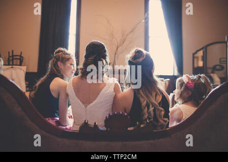 Rear view of bride sitting with bridesmaids and flower girl on sofa at home - Stock Photo