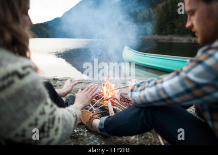 Young couple warming hands by campfire at lakeshore - Stock Photo