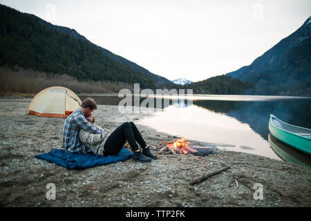 Boyfriend embracing girlfriend while sitting on picnic blanket at lakeshore by campfire against clear sky