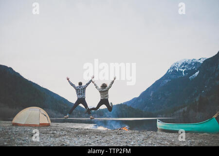 Rear view of happy young couple with arms raised jumping at lakeshore against clear sky during dusk - Stock Photo